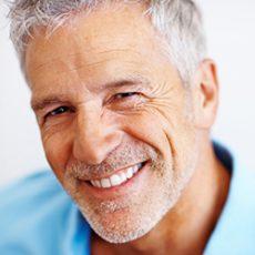 Closeup portrait of a happy mature man on white background